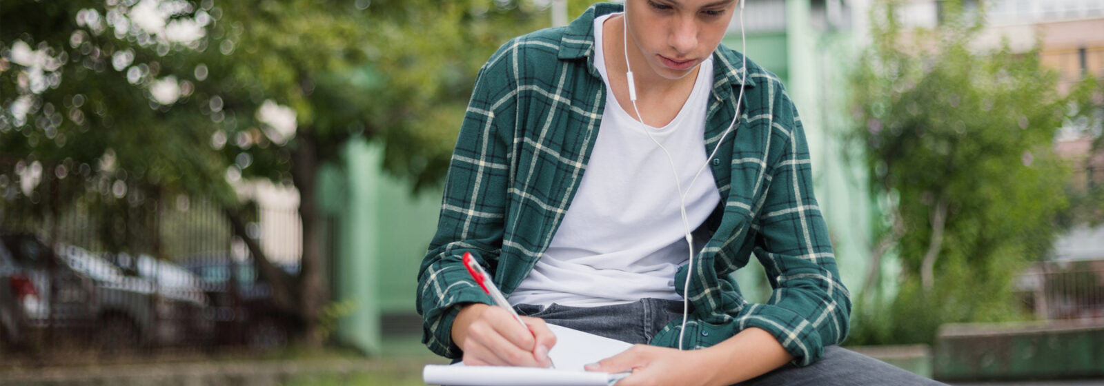 Teenage boy writes in a notebook while listening to music