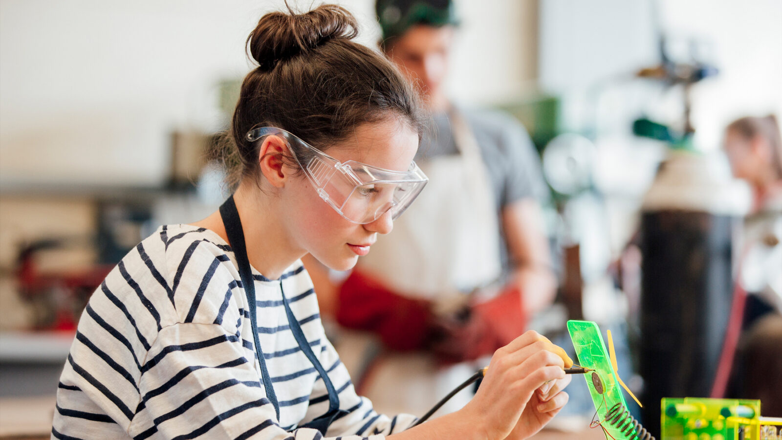 Girl wearing safety glasses doing soldering